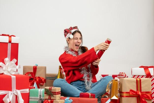 Glückliches partygirl mit weihnachtsmütze unter verwendung von party popper, der um geschenke auf weiß sitzt