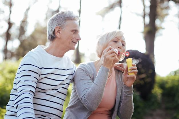 Glückliches pensioniertes lustiges paar, das sich umarmt und seifenblasen macht, während es das wetter im park genießt und liebe ausdrückt