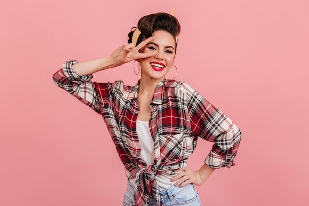 Glückliches pinup-mädchen, das mit friedenszeichen aufwirft. studioaufnahme der lachenden schönen frau im roten karierten hemd.