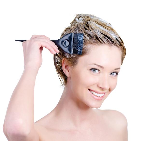 Glückliches porträt der fröhlichen schönen jungen frau mit pinsel, die ihr haar färbt - lokalisiert auf weiß