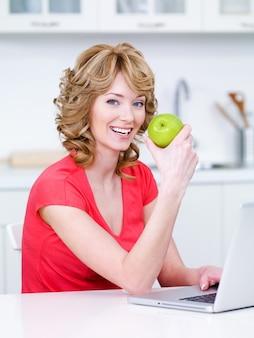 Glückliches porträt der jungen schönen frau, die in der küche sitzt und grünen apfel isst
