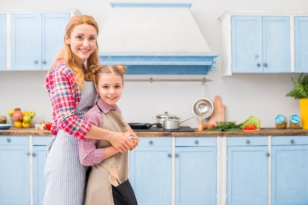 Glückliches porträt der mutter und der tochter, welche die kamera steht in der küche betrachtet