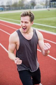 Glückliches porträt des aufgeregten jungen mannes, der seine faust im stadion zusammenpreßt