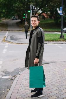 Glückliches porträt des lächelnden jungen mannes, der auf dem bürgersteig hält grüne einkaufstasche steht