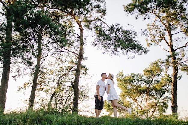Glückliches porträt des liebenden paares auf einem spaziergang im park an einem sonnigen tag.
