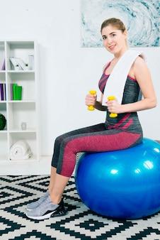 Glückliches porträt einer dünnen jungen frau, die auf dem blauen pilates ball trainiert mit dummköpfen auf teppich sitzt