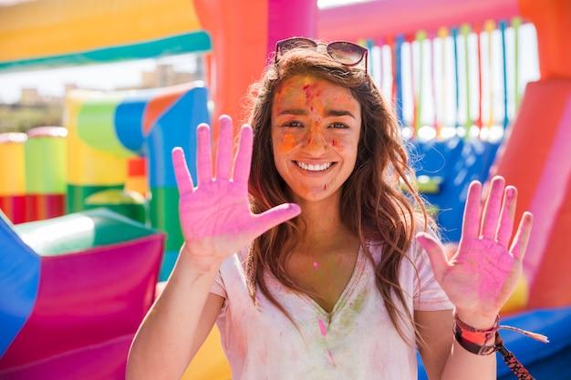 Glückliches porträt einer jungen frau, die holi farbhände zeigt