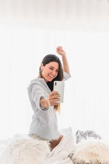 Glückliches porträt einer jungen frau, die selfie auf smartphone nimmt