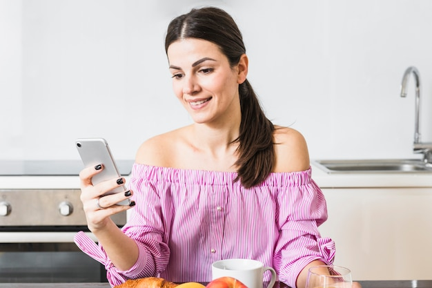 Glückliches porträt einer jungen frau, die zu hause mobiltelefon verwendet