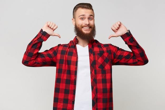 Glückliches porträt eines fröhlichen, fröhlichen, freudigen, stolzen, bärtigen mannes in einem karierten hemd, das fäuste ballt und daumen auf sich selbst zeigt, wie ein gewinner mit vor vergnügen geschlossenen augen, isoliert über weißem hintergrund
