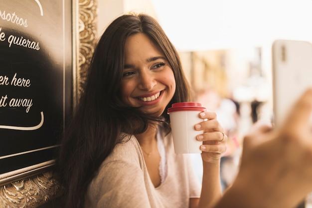Glückliches porträt eines mädchens, das mitnehmerkaffeetasse hält