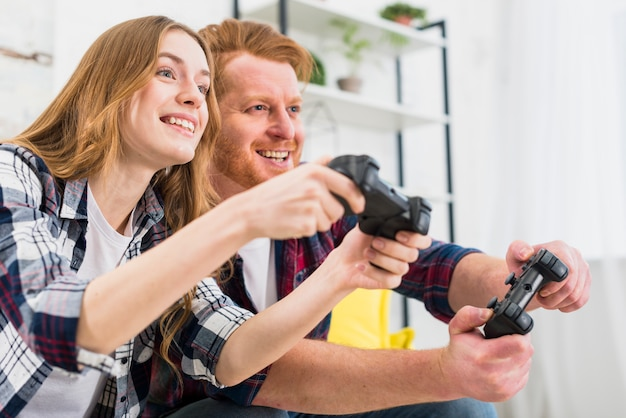 Glückliches porträt von den jungen paaren, die spielkonsole mit steuerknüppeln spielen