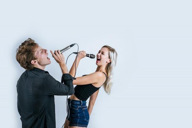 Glückliches porträt von den paaren, die mikrofon halten und singen ein lied