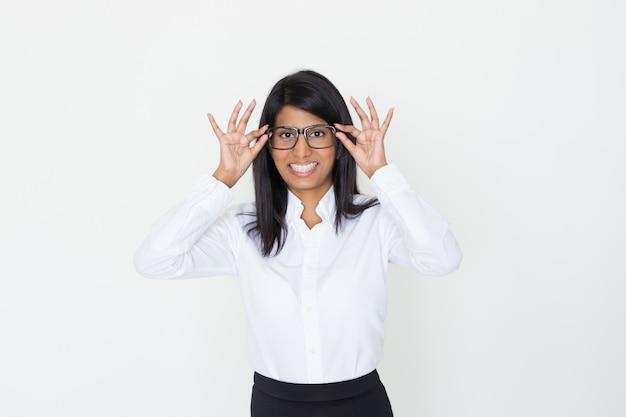 Glückliches positives büromädchen, das auf brillen sich setzt