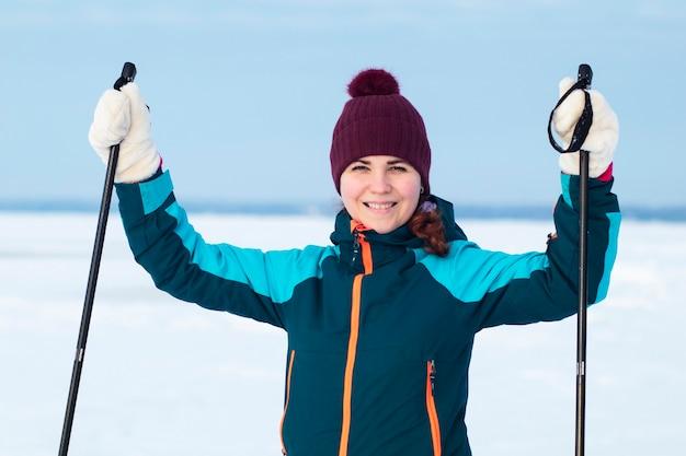 Glückliches positives frauenskifahren im winter warme kleidung und hut draußen an kaltem sonnigem tag