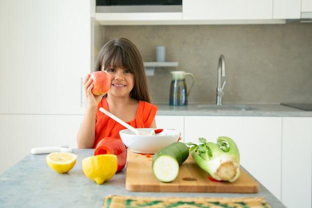 Glückliches positives mädchen, das am küchentisch mit geschnittenem frischem gemüse steht und apfel hält und zeigt, lächelnd, kamera betrachtend. gesundes ernährungskonzept