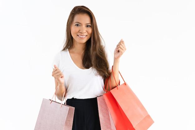 Glückliches positives mädchen, das das einkaufen genießt
