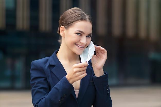 Glückliches positives mädchen, junge schöne hübsche geschäftsfrau hebt ab oder setzt schützende sterile medizinische maske auf gesicht im freien auf, lächelnd.