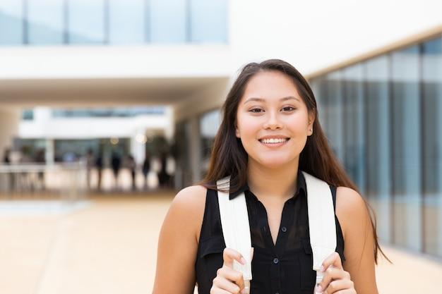 Glückliches positives studentenmädchen, das draußen geht