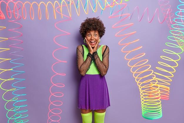 Glückliches reaktionskonzept. die fröhliche dunkelhäutige frau hält die hände auf den wangen, starrt mit überglücklichem gesichtsausdruck und trägt ein farbenfrohes outfit