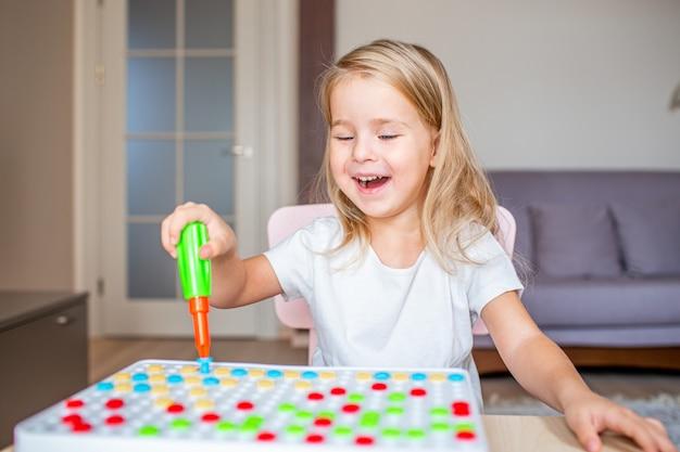 Glückliches recht kleines blondes mädchen, das zu hause an einem tisch spielt mit einem spielzeugschraubenzieher und mehrfarbenschrauben mit einem strahlenden lächeln sitzt. frühe erziehung.