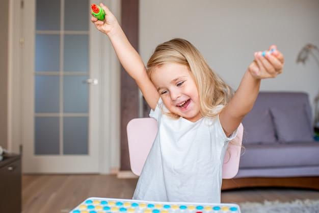 Glückliches recht kleines blondes mädchen, das zu hause an einem tisch spielt mit einem spielzeugschraubenzieher und mehrfarbenschrauben sitzt. frühe erziehung.
