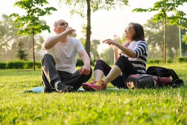 Glückliches reifes paar, das im park auf fitnessmatte sitzt und trinkenden joghurt ruht