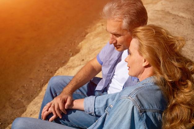 Glückliches reifes paar, das mit ihren hunden auf dem see in der sonne sitzt. konzept des familienurlaubs in der natur