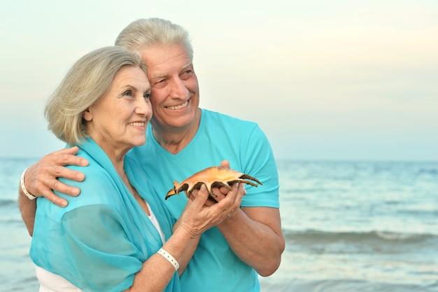 Glückliches reifes paar genießt frische luft am strand mit muschel