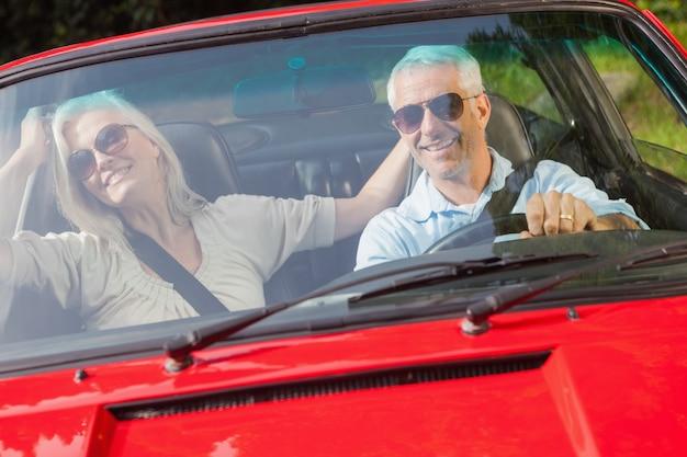 Glückliches reifes paar im roten cabriolet