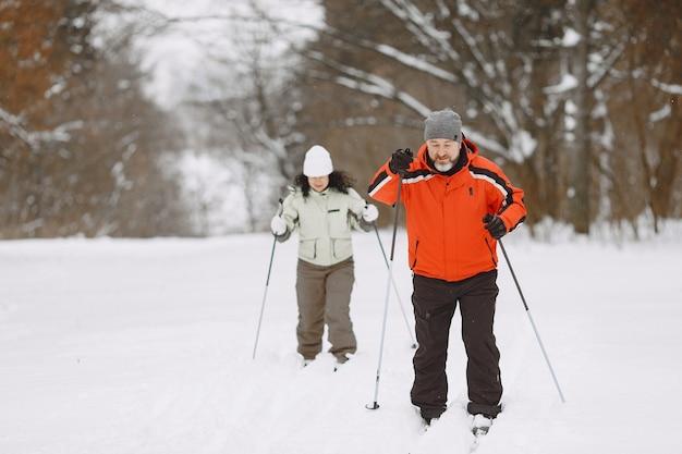 Glückliches reifes paar im winterpark. die leute tragen trekking im wald in ihrer freizeit
