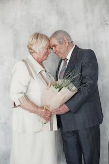 Glückliches reifes paar in der liebe umarmend, grauhaariger ehemann und ehefrau. ältere frau, die einen blumenstrauß hält.