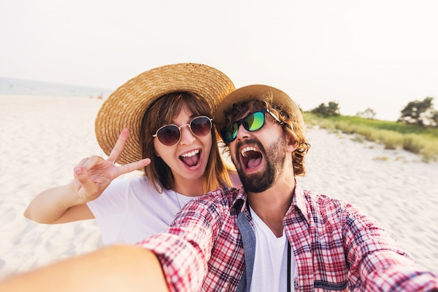 Glückliches reisendes paar in der liebe, die ein selfie am telefon am strand nimmt