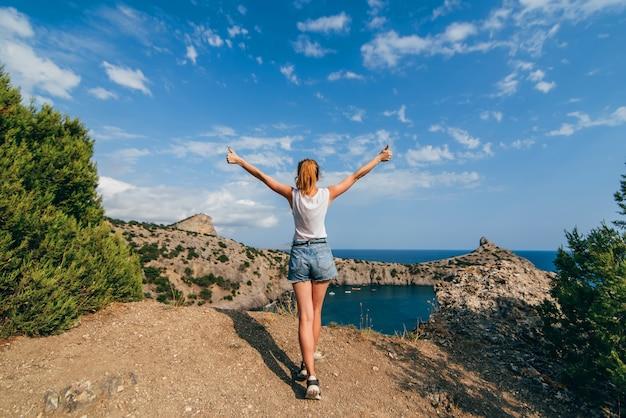 Glückliches reisendmädchen mit den angehobenen händen, die auf einen berg über dem meer in den sommerferien stehen