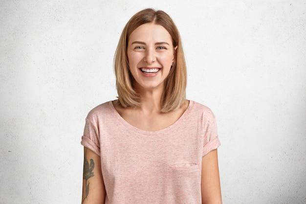 Glückliches reizendes hübsches junges weibliches modell mit wackelfrisur und strahlendem lächeln, gute laune nach erfolgreichem einkauf, gekleidet in lässigem losem t-shirt