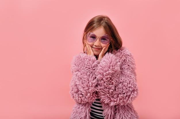 Glückliches reizendes kleines mädchen, das runde brille und pelz trendigen mantel posiert, der aufwirft