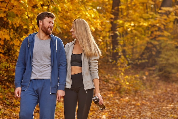 Glückliches reizendes paar, das spaziergang im wald genießt, gespräch nach dem laufen hat