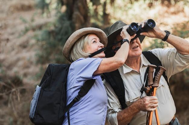 Glückliches rentnerehepaar, das die natur im kalifornischen wald genießt