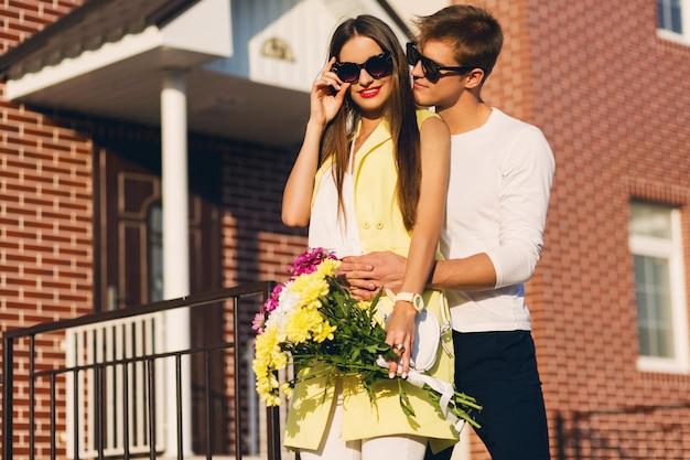 Glückliches romantisches paar, das draußen in der europäischen stadt am abend umarmt. junge hübsche frau, die blumen hält. paar in der liebe aus.