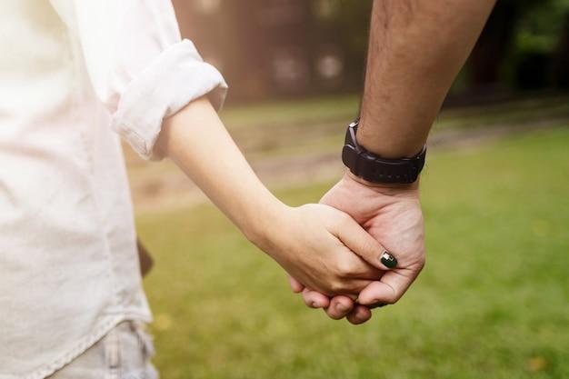Glückliches romantisches paar im liebeshändchenhalten und zusammen in park gehen