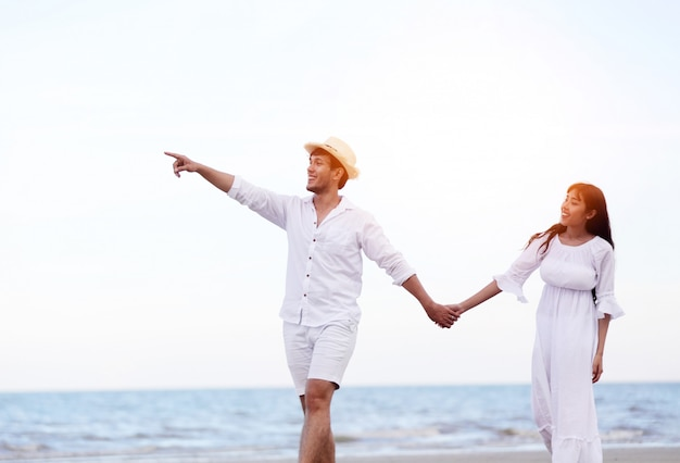 Glückliches romantisches paarliebhaberhändchenhalten, das zusammen auf den strand geht