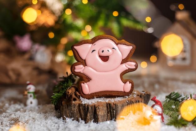 Glückliches rosa schwein des lebkuchen in gemütlicher warmer dekoration mit girlandenlichtern
