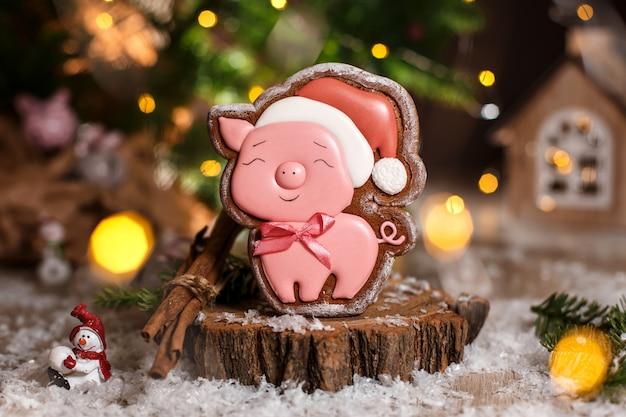 Glückliches rosa schwein des lebkuchens im weihnachtshut in der gemütlichen warmen dekoration mit girlandenlichtern
