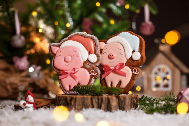 Glückliches rosa schwein des lebkuchens zwei im weihnachtshut in der gemütlichen warmen dekoration mit girlandenlichtern
