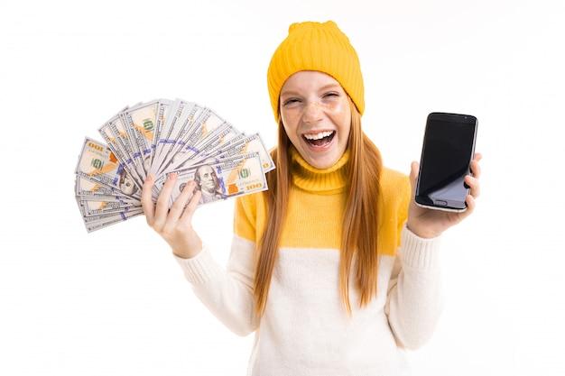 Glückliches rothaariges mädchen, das geld und ein telefon mit modellhänden auf weiß hält
