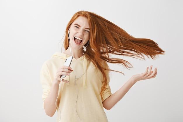 Glückliches rothaariges mädchen, das karaoke-app-spiel auf smartphone spielt und lied in kopfhörern singt