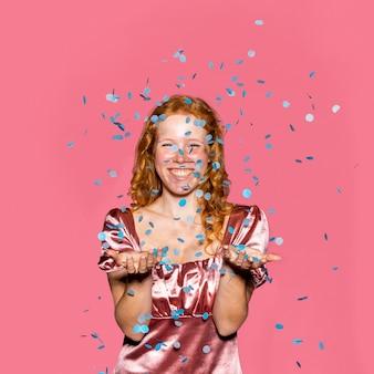 Glückliches rothaariges mädchen, das konfetti wirft