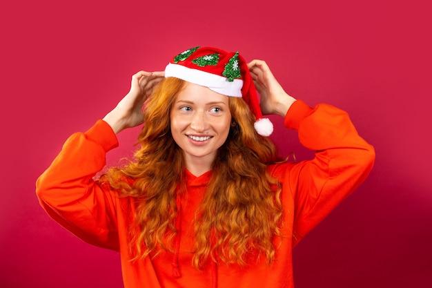 Glückliches rothaariges mädchen, mit einem hellen lächeln und herrlichem lockigem haar, in einem weihnachtsmannhut auf einer roten wand. urlaubskonzept.