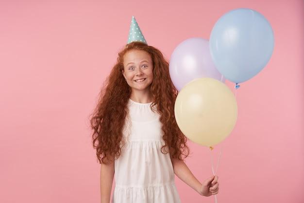 Glückliches rothaariges weibliches kind mit langem lockigem haar, das über rosa hintergrund in festlicher kleidung und geburtstagskappe aufwirft, luftballons in der hand hält und wahre positive emotionen ausdrückt