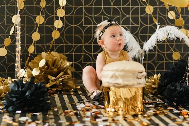 Glückliches säuglingsbaby, das ihren ersten geburtstag feiert.